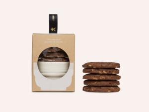 La boîte l'heure du goûter avec un bol atelier Pierre Culot à l'intérieur et une pile de cookies chocolat.