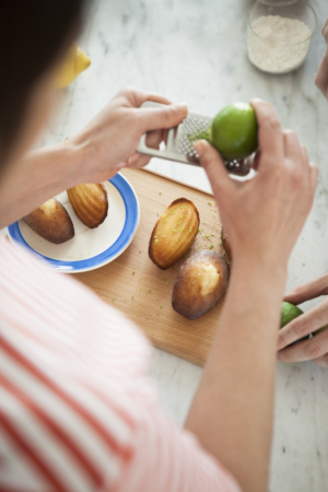 A person putting lime zests on madeleines placed on a chopping board.