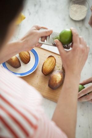 Personne mettant des zestes de citron vert sur des madeleines disposées sur une planche à découper.