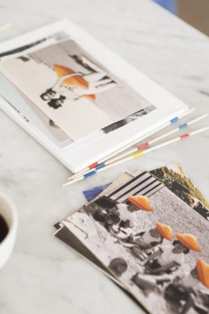 De vieilles cartes postales sur une table, d'une famille en vacances avec une grosse madeleine ajouté en photomontage.