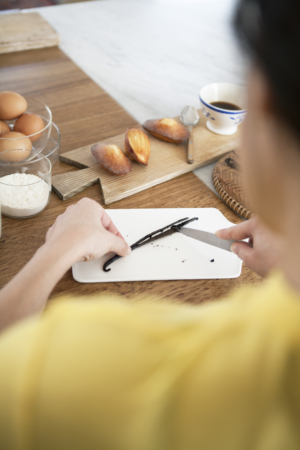 A person cutting a vanilla pod on a chopping board next to madeleines and a cup of coffee.