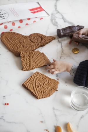 Kleine meisjeshanden die een chocolade Sinterklaas en stukjes van een speculoos van de Sint grijpen.