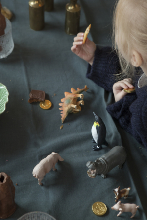 Little girl eating biscuits at a table full of animal figurines.