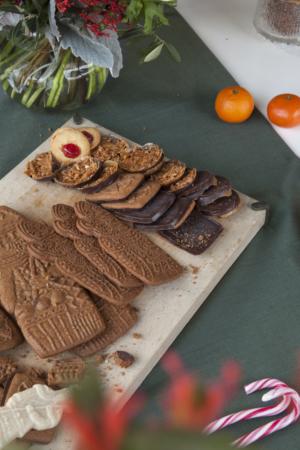 Verschillende maten Sinterklaas en enkele Dandoy koekjes op een snijplank, met daarnaast clementines, bloemen en suikerriet.