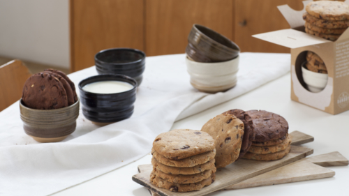 A table at snack time, a bowl full of milk, pile of cookies, the Milk and Cookies Box.