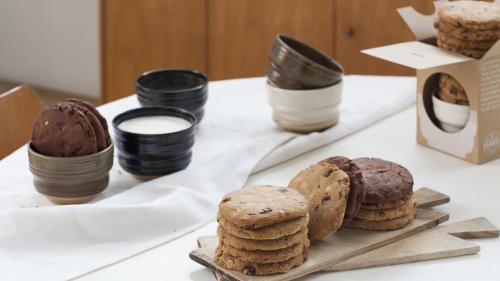 Table à l'heure du goûter, dessus des piles de cookies, un bol rempli de lait, des bols entassés, la boîte L'heure du goûter.