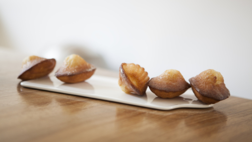 Madeleines placed on a chopping board.