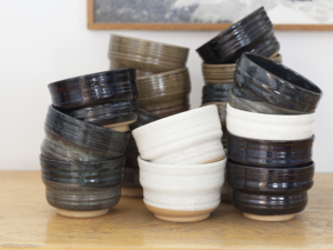 Five piles of shagreen, white, black blue, tomato and khaki bowls on a wooden table, in the back a white wall and a frame.