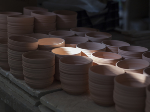Piles of bowls in the shadow, a sunshine illuminates a few of them.
