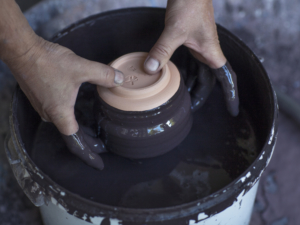A pair of hands plunging a bowl into a pot of black blue paint.