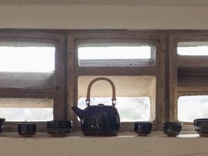On a window sill inside Atelier Pierre Culot, a tea pot, cups and bowls.